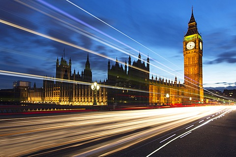 Houses of Parliament and Big Ben floodlit at night with colourful light trails from passing traffic on Westminster Bridge, London, England, United Kingdom, Europe
