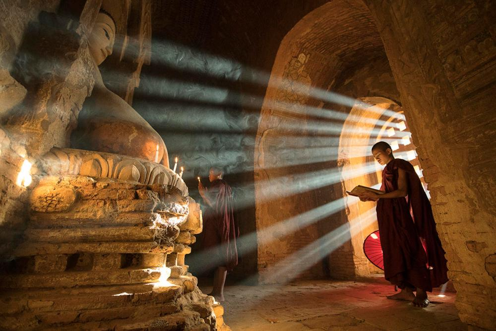 Two monks praying in a temple image