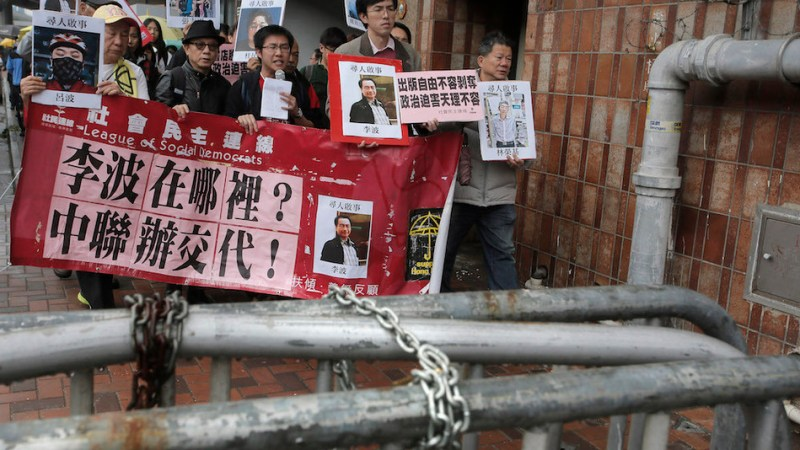 "Protesters hold photos of missing booksellers during a protest outside the Liaison of the Central People's Government in Hong Kong, Sunday, Jan. 3, 2016. Hong Kong pro-democracy lawmakers say they'll press the government for answers after a fifth employee of a publisher specializing in books critical of China's ruling communists went missing. The Chinese words on banner reads ""Where is Lee Bo? Liaison of the Central People's Government of Hong Kong explain!""(AP Photo/Vincent Yu)"