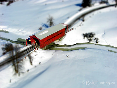 This covered bridge is found on Chemin Cross Loop south of Wakefield, Québec. It is not to be confused with the larger covered bridge just to the north of Wakefield. Again, the foreground and background have been blurred to shorten the apparent depth of field and the red colour of the bridge has been saturated to the point of synthetic toy look-alike.
