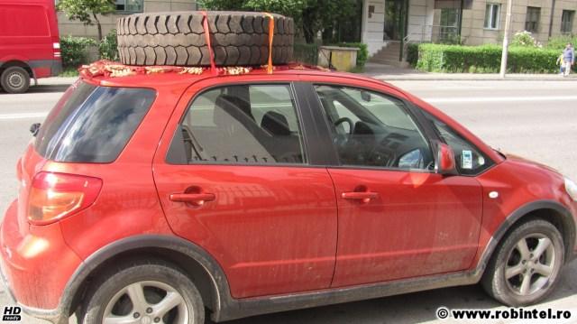 O mașină mică transportând un cauciuc mare, de camion, pe caroserie