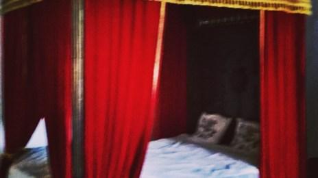 Pat regal, cu baldachin roșu, expus la Castelul de la Hunedoara
