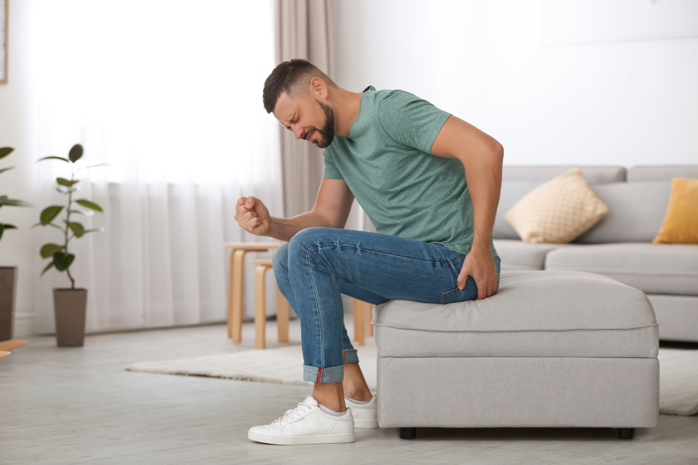 man seated in pain