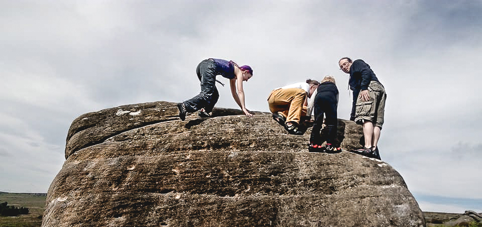 Climbers looking into a pocket with a caterpillar in at the top of The Sheep Slab