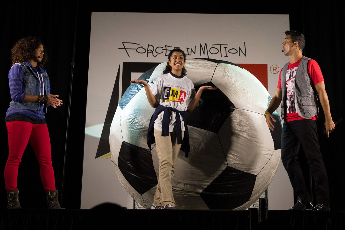 "With the help of a student participant, ""FMA Live!"" crew members explain Newton's second law of motion during the same performance. ""FMA Live!"" is a program sponsored by NASA and Honeywell that teaches Newton's three laws of motion mixed with dance and music. Image: NASA/Jay Westcott"