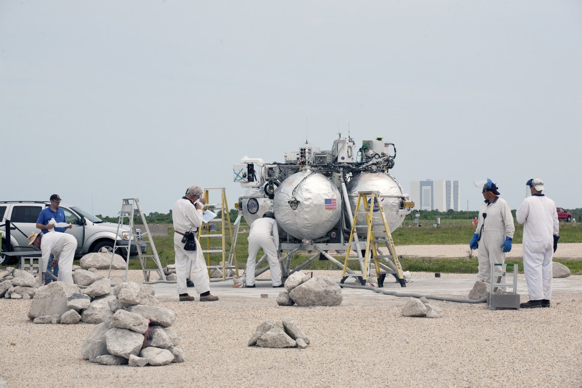 Engineers and technicians check the Project Morpheus prototype lander after it touched down on a dedicated landing pad inside the hazard field at the Shuttle Landing Facility at Kennedy Space Center. Morpheus launched on a free-flight test from a new launch pad at the north end of the facility.  Credit: NASA/Kim Shiflett