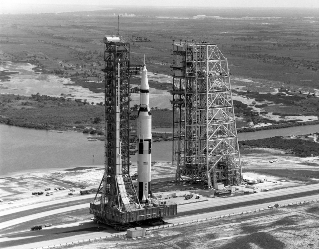 While traversing the 3.5 mile crawlerway to LC 39-A, the Saturn V passes the Mobile Service Structure, which will join it atop the pad as launch preps are continued.
