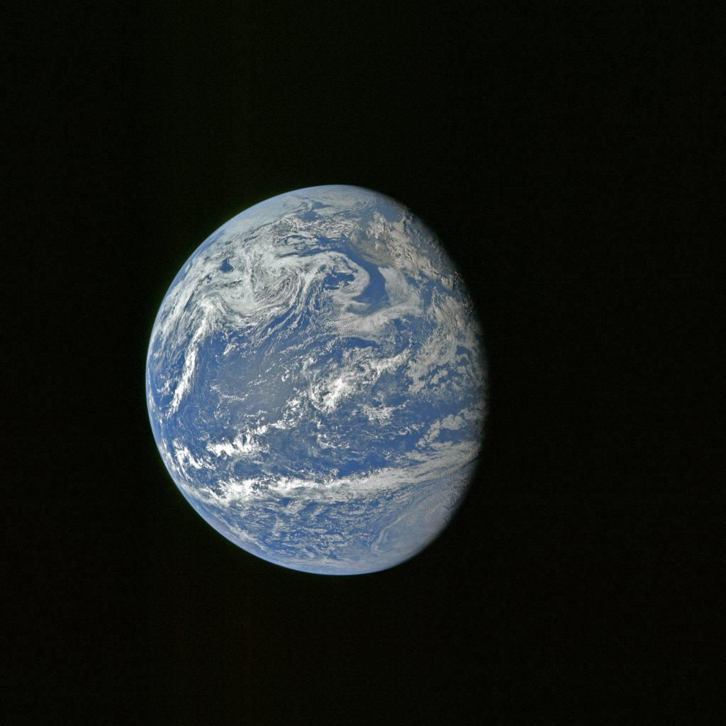 Earth is captured through the astronauts' camera during the translunar journey toward the Moon.