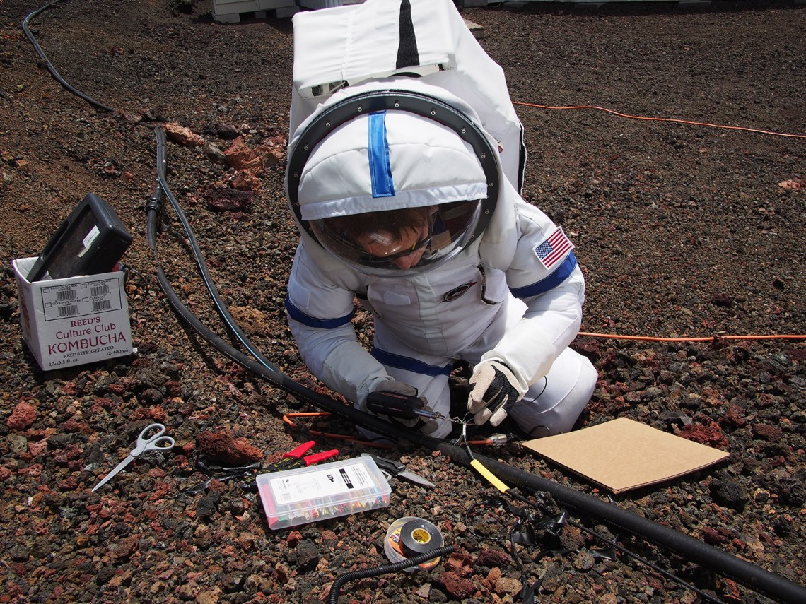 Ross Lockwood splices a cable during an EVA outside the HI-SEAS habitat. While this is a fairly simple operation for an electrician here on Earth, it is made much more difficult when wearing a full spacesuit. Credit: Casey Stedman