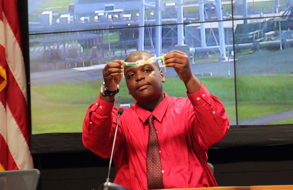 Zaire McQueen, from Milton Olive Middle School, Wyandanch Union Free School District, NY, hold sup and describes the experiment for which he is the co-principal investigator. Credit: Lloyd Campbell