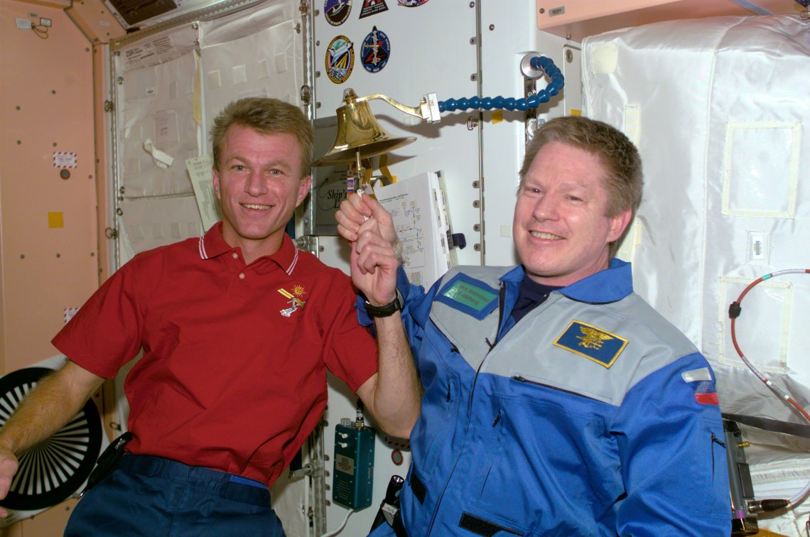 Astronauts Brent W. Jett, Jr. (left) and William M. Shepherd participate in an old Navy tradition of ringing a bell to announce the arrival or departure of someone to a ship.The bell is mounted on the wall in the Unity node of the International Space Station (ISS). Credit: NASA