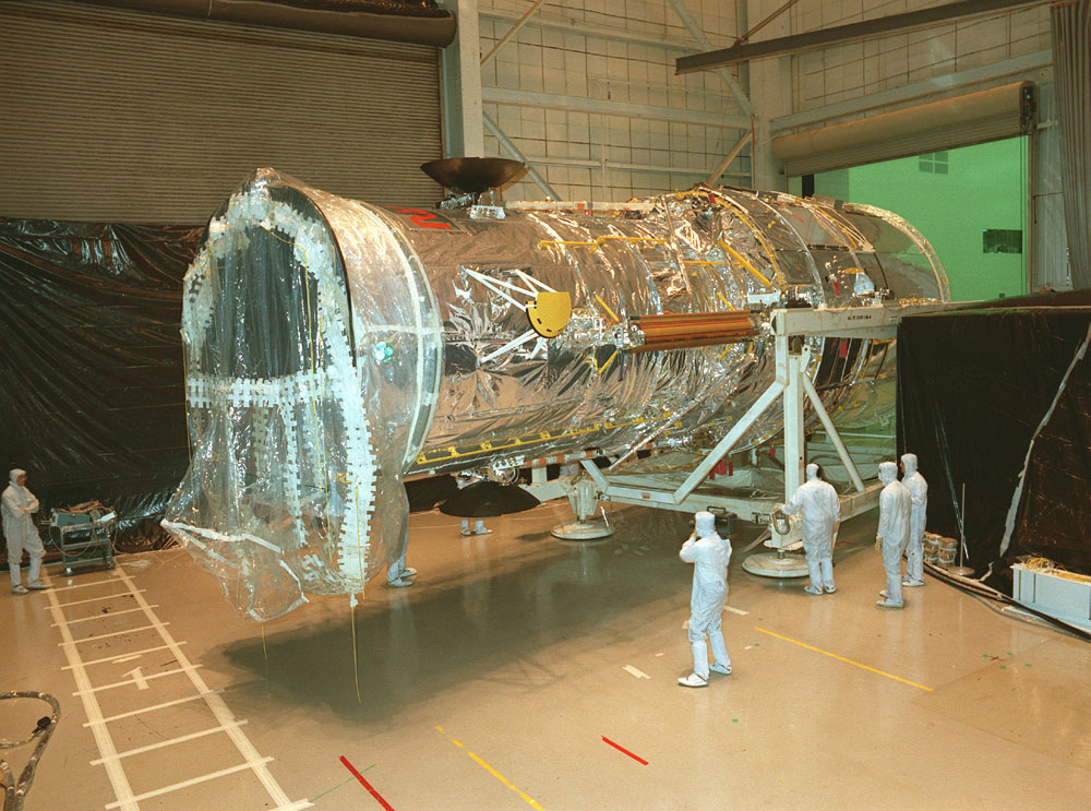Hubble being transferred from the Vertical Assembly Test Area (VATA) to the High Bay at the Lockheed assembly plant in preparation for transport to the Kennedy Space Center (KSC) after final testing and verification.