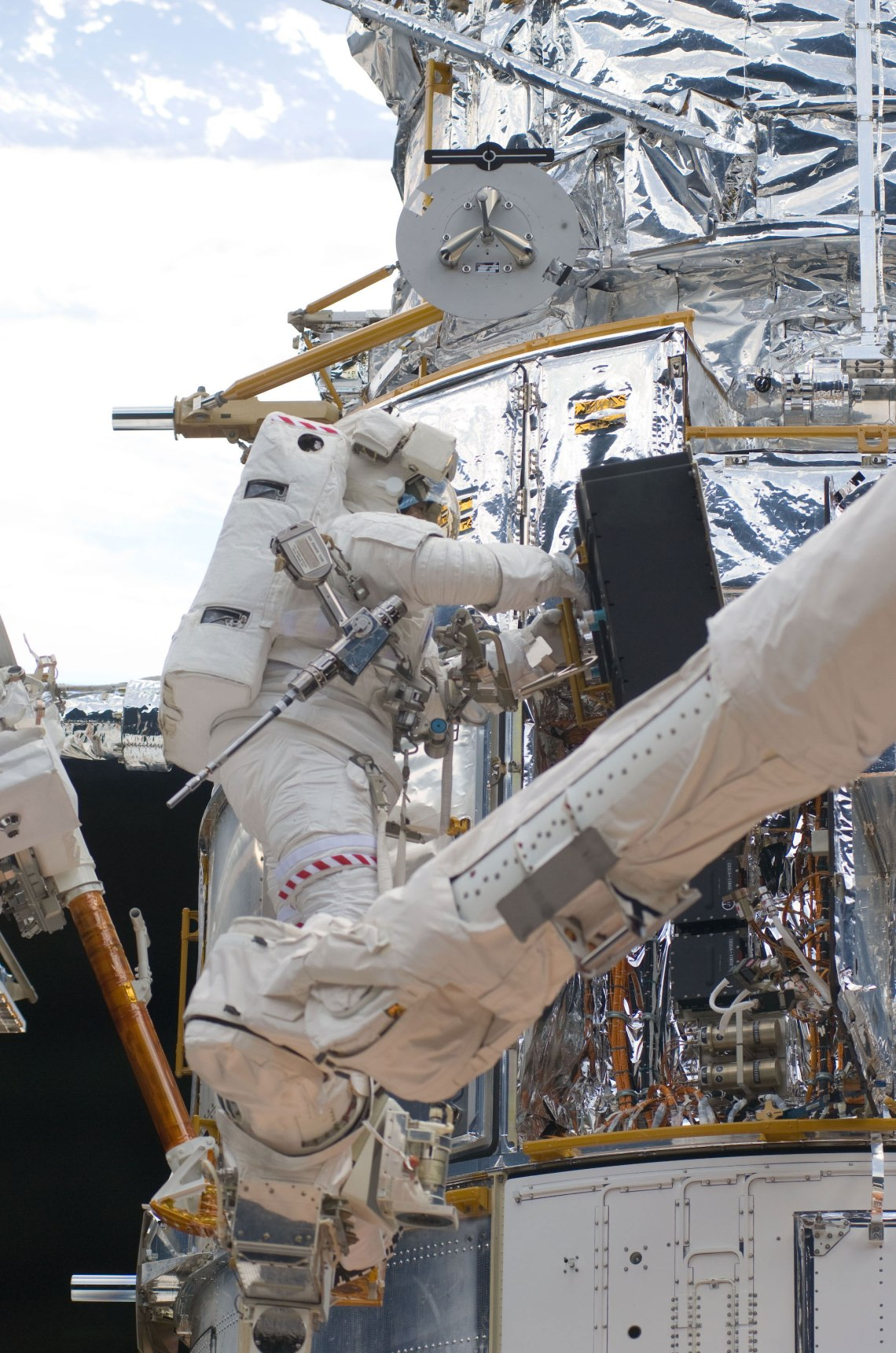 While standing on the end of Atlantis' RMS arm, STS-125 mission specialist Michael Good works on the Hubble Space Telescope. Good and fellow mission specialist Mike Massimino (out of frame) continue work on the HST, locked down in the orbiter's cargo bay. Credit: NASA