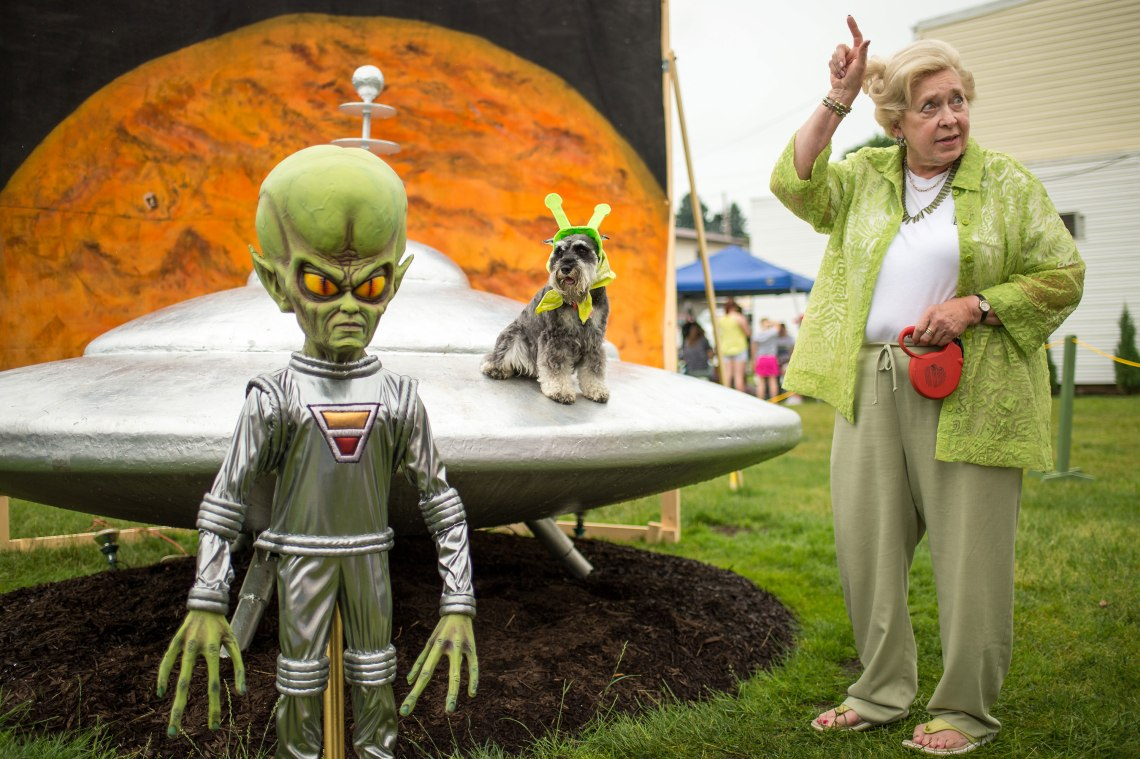 "Sue Morris and her dog ""Pepper"" are seen with a model of a spacecraft and alien used for photos during the Mars New Year's celebration Saturday, June 20, 2015, in Mars, Pennsylvania. Credit: NASA/Bill Ingalls"