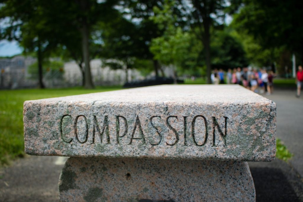 """stone bench with the word """"compassion"""" carved in it"""