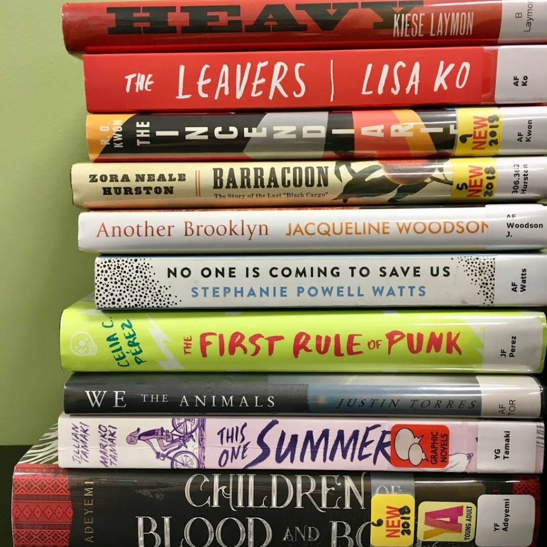 Stack of books with the spines out, showing titles.