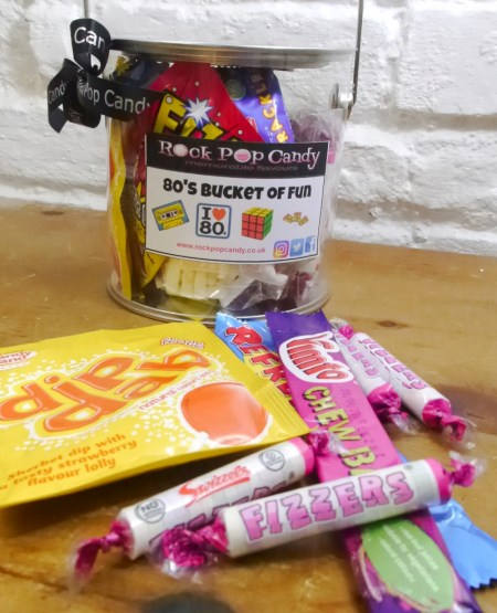Image of the 80s bucket of fun. Selection of retro sweets in clear plastic paint tin