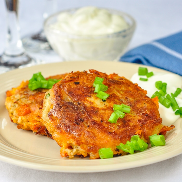 Onion Cheddar and Bacon Potato Cakes photo of two potato cakes on a beighe plate with sour cream in the background