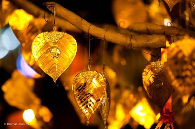 Des prières ainsi que la date du jour sont inscrites sur des feuilles dorées puis suspendues à un arbre.