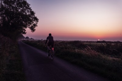 A smouldering red sun emerges from the violet haze, at dawn on this little country lane near the hamlet of Rickney, in East Sussex