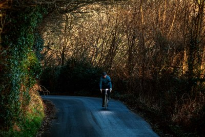 Bicycles in the landscape series - a cyclist pedals up a steep hill on a narrow country lane with daw lightweight illuminating the branches overhead
