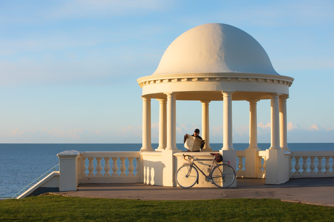 Man with bicycle reading map in old dome by seaside