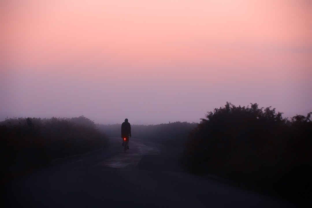 red taillight of cyclist disappearing into mist on the marsh