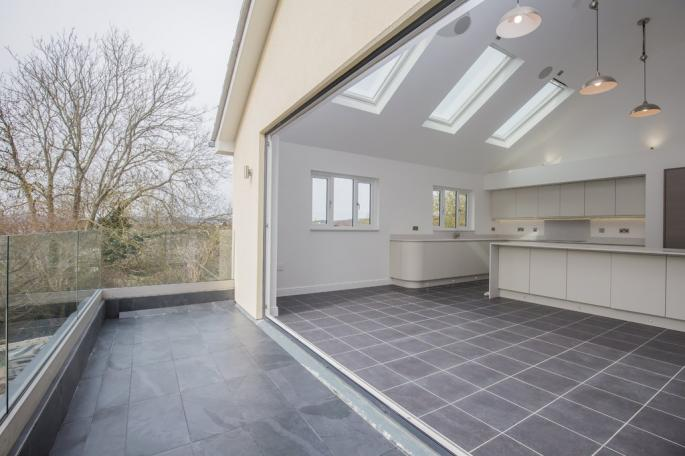 Full-height bi-fold and sliding doors link the kitchen and dining area to the outside balcony