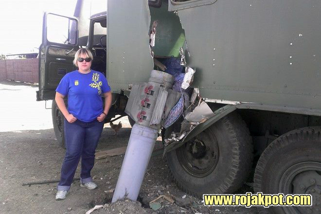 Ukrainian girl posing next to the dud rocket