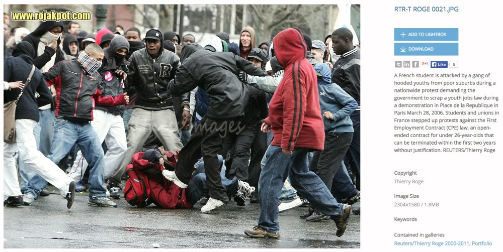 A French student is attacked by a gang of hooded youths from poor suburbs during a nationwide protest demanding the government to scrap a youth jobs law during a demonstration in Place de la Republique in Paris March 28, 2006. - REUTERS / Thierry Roge