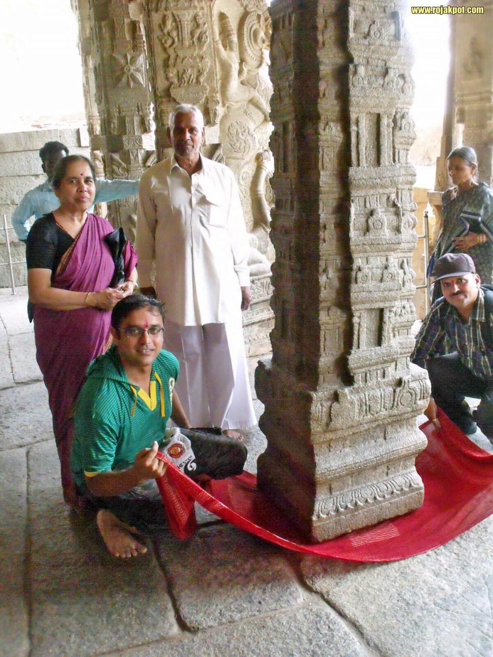 A family posing after proving that yes, their cloth too will pass under the hanging pillar of Lepakshi Temple
