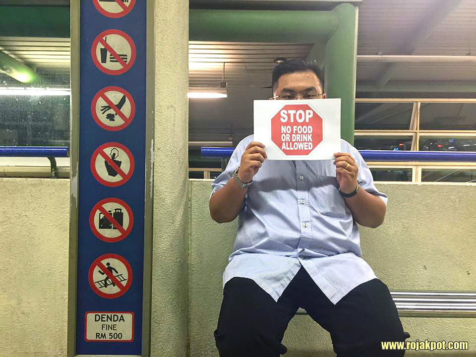 Dato Melvin Loh Kok Man holding a No Eating sign at an LRT station