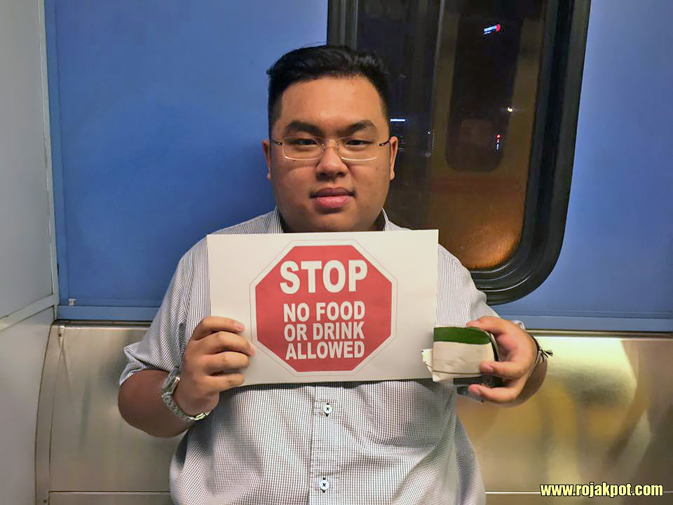 Dato Melvin Loh Kok Man holding a No Eating sign on an LRT