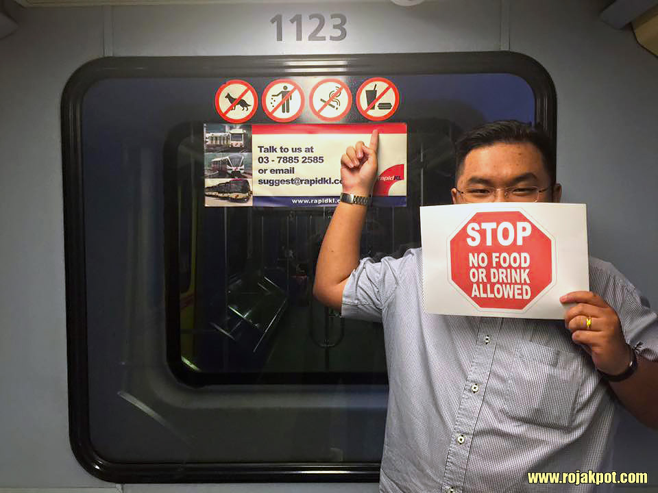 Dato Melvin Loh Kok Man pointing at the No Eating sign on an LRT
