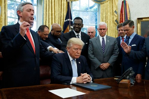 FILE - In this Sept. 1, 2017 file photo, religious leaders pray with President Donald Trump after he signed a proclamation for a national day of prayer to occur on Sunday, Sept. 3, 2017, in the Oval Office of the White House in Washington.  As the threat of impeachment looms, President Donald Trump is digging in and taking solace in the base that helped him get elected: conservative evangelical Christians who laud his commitment to enacting their agenda. (AP Photo/Evan Vucci, File