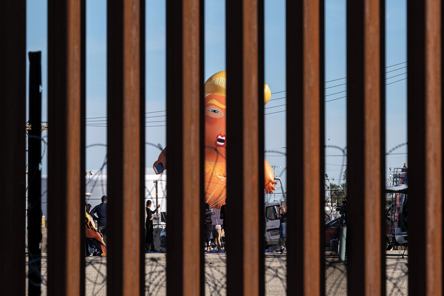 TOPSHOT - A satirical balloon of a baby US President Donald Trump is seen through the US-Mexico border fence during a demonstration against him prior to his visit to Calexico, California, as seen from Mexicali, Baja California state, Mexico, on April 5, 2019. - President Donald Trump flew Friday to visit newly built fencing on the Mexican border, even as he retreated from a threat to shut the frontier over what he says is an out-of-control influx of migrants and drugs. (Photo by Guillermo Arias / AFP) (Photo by GUILLERMO ARIAS/AFP via Getty Images)