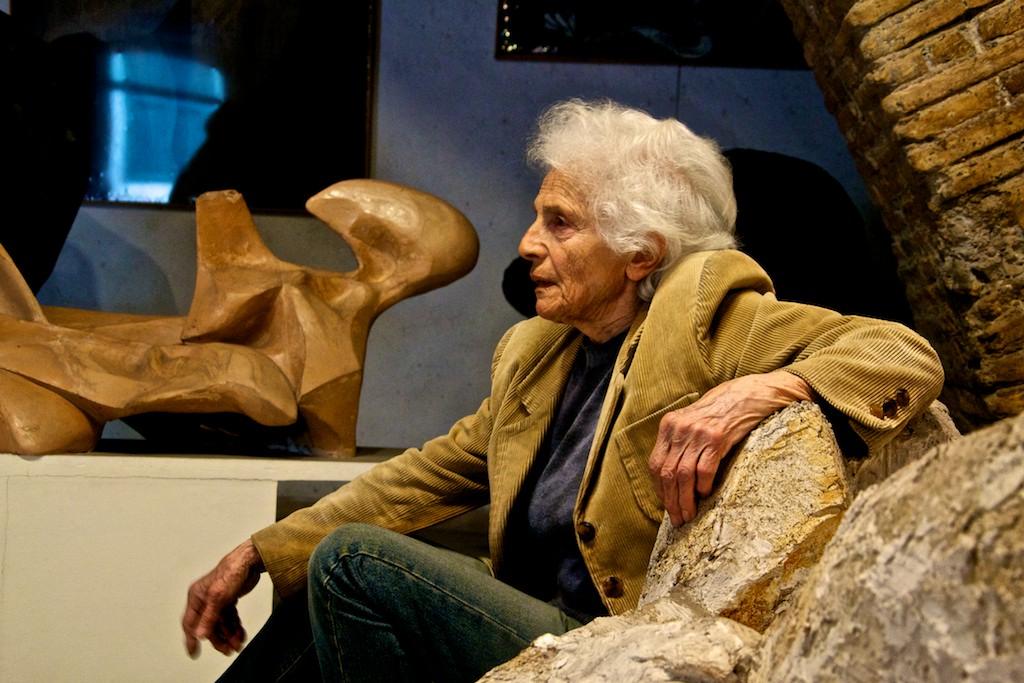 Scultrice di profilo seduta su una delle sue opere con giacca di velluto ocra a coste e capelli bianchi scapigliati