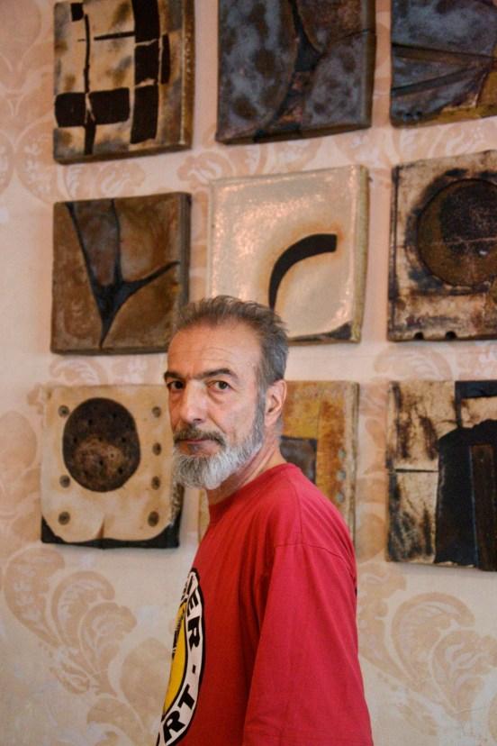 Uomo scultore con tshirt rossa davanti le sue opere di ceramica guarda serio nell'obiettivo.