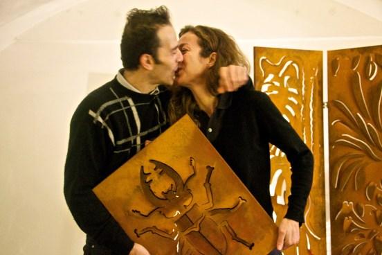 Un uomo e una donna vestiti di nero si baciano con in braccio una loro creazione che rappresenta un cervo volante in ferro trattato tipo ruggine.