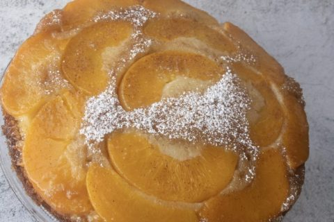 Upside down peach cake decorated iwth icing sugar