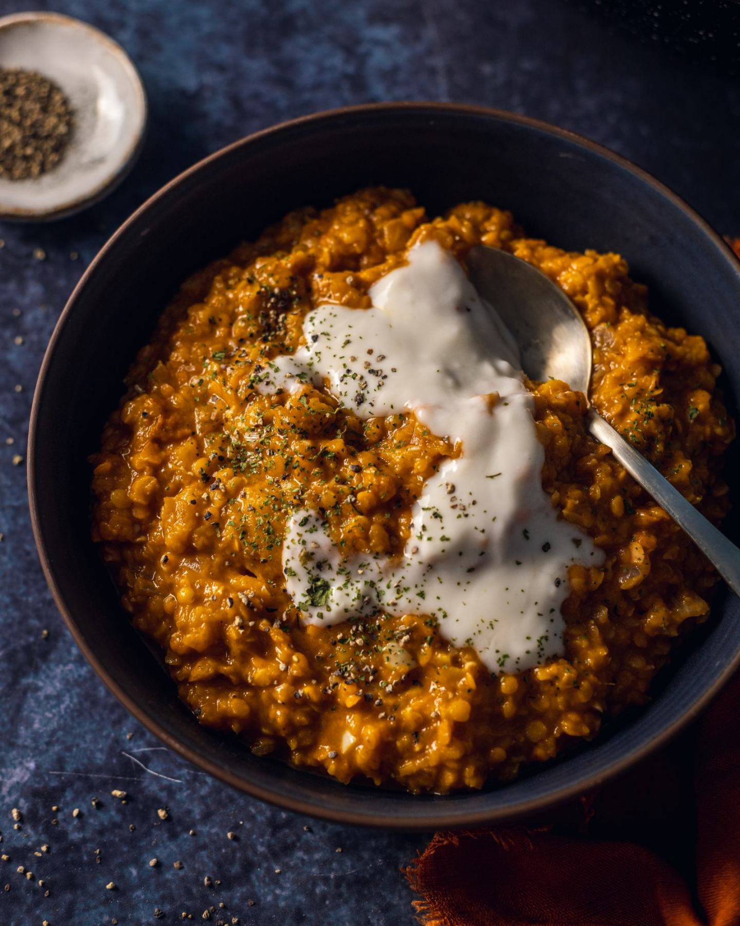 a plate full of Roasted Pumpkin Red Lentil Dhal placed on a dark blue background, with a spoon and coconut yoghurt on the top