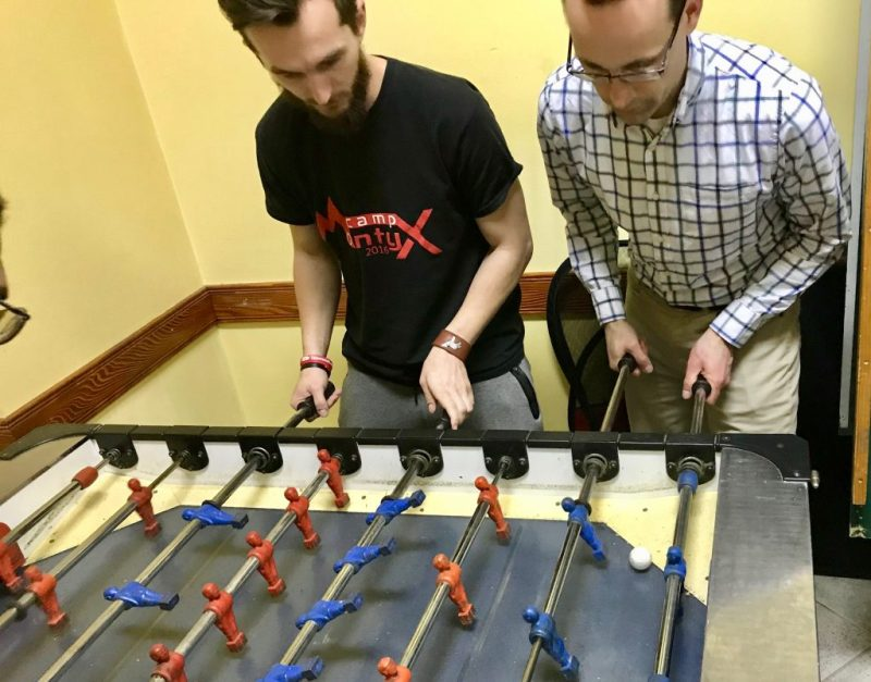Two men avidly playing foosball