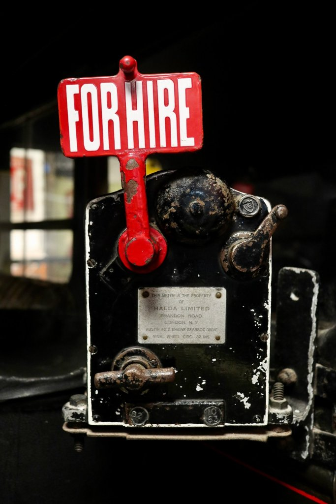 "Red ""For Hire"" sign pops up from antique machine--a symbol for our times."
