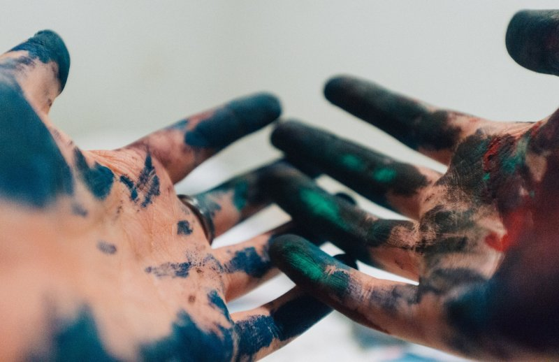 Open hands covered in blue and green paint.
