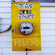 """Jesus Saves"" painted on a yellow gas meter"