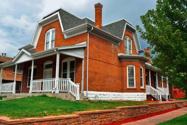 Jerkinhead Roof on a Colonial Revival Style Home with Brick Siding