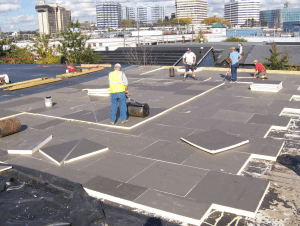 """The roof insulation panels were """"walked-in"""" immediately following placement and periodically """"rolled"""" with a counterweight to ensure a satisfactory bond to the deck."""