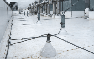 Cables interconnect the air terminals (on top of the parapet) to roof penetration (foreground) and other metal items, such as the rooftop exhaust fans and their anchorage points. Interconnections are vital to the function of the lightning protection system.