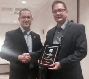 John Ferraro (left), Roof Coatings Manufacturers Association executive director, awards Benjamin Borns of Sherwin-Williams the inaugural Emerging Leader Award.
