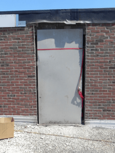 PHOTO 6: Even the existing door was low to the existing roofing at SD 113 Deerfield High School. Here the door frame has been removed; the door has been placed for interior protection.